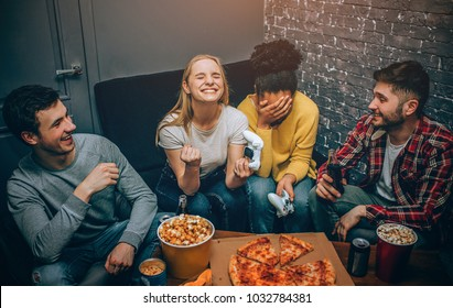 An emotional picture wher blonde girl wins and afroamerican girl loses. One of them is happy about winning the game while the other one is upset. Boys are just having some fun. Gamers. Night party.