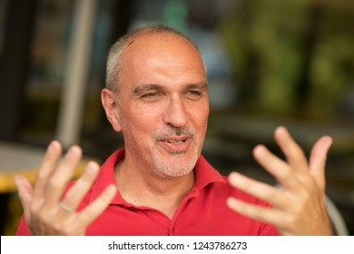 Emotional portrait of an active and ridiculous mature tanned European man with a bald head, explaining the violently gesticulating to a friend his idea while sitting in a street cafe. Summer.Lifestyle