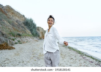 emotional portrait american woman at wild beach spontaneous laughing and smiling, high spirits and wellness concept