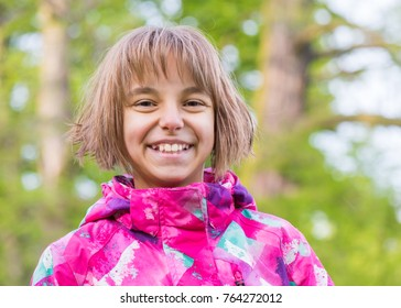 Emotional portrait of attractive caucasian little student girl with beautiful brown eyes in spring city park. Funny cute smiling child looking at camera - close-up, outdoors.
