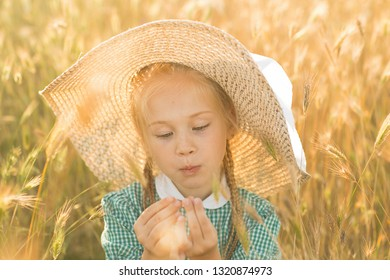 Emotional portrait of a beautiful and funny little blonde girl looking with surprise at wheat spikelets illuminated by the rays of the setting sun. Summertime. Summer vacation. Happy childhood