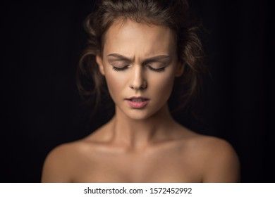 Emotional portrait of a beautiful girl against a background in studio