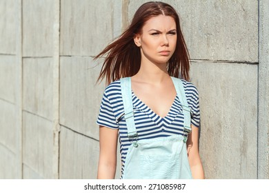 Emotional portrait of a beautiful girl on a background of a concrete wall