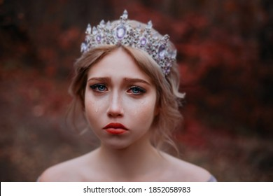 Сlose-up emotional portrait of beautiful sad girl princess crying. Fairy woman medieval queen. Wet red eyes, tears streaming down her cheeks on attractive face. Vintage crown tiara on head blonde hair