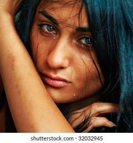 Emotional portrait of the beautiful young suntanned woman with scars on hands and tears on the face