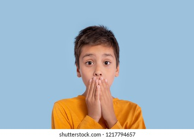 Emotional portrait of the boy wearing in a yellow shirt on a blue background in studio. He has clamped palms to himself a mouth and with amazement looks at camera, having heard unexpected news.