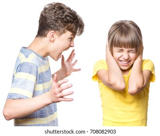 Emotional portrait of brother and sister, quarreling children - teen boy shouting at little girl. Negative human face expression. Conflict concept.