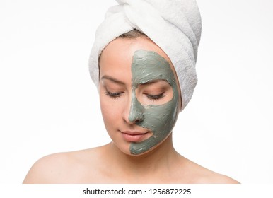 Emotional portrait of a calm and gentle nude young woman with a blue clay cosmetic mask on her face looking down while applying isolated on white background. Lifestyle. Beauty procedure. Positive