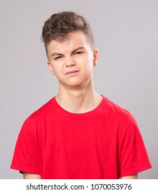 Emotional portrait of caucasian upset problem teen boy. Sad boy looking at camera. Worried  child wearing red t-shirt, on gray background.