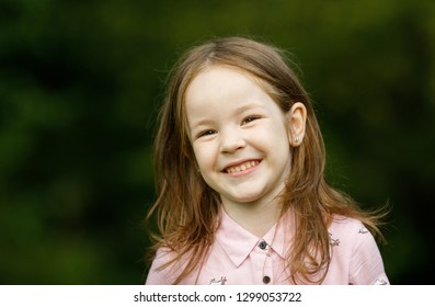 Emotional portrait of a cheerful and happy little girl, looking forward laughing against the background of blurred foliage on a walk in the park. Happy childhood. Positive emotions and energy. Summer