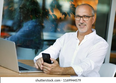 Emotional portrait of a confident and positive business mature European man with a bald head and wearing glasses, looking with a smile at the camera holding a smartphone sitting at a table in a cafe