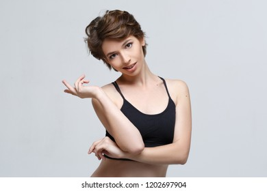 Emotional portrait of a confident woman isolated on gray background.