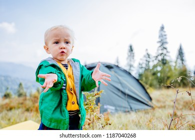 Emotional portrait of cute toddler boy traveler in camping with tent on background. Travel with child, health relations concept.