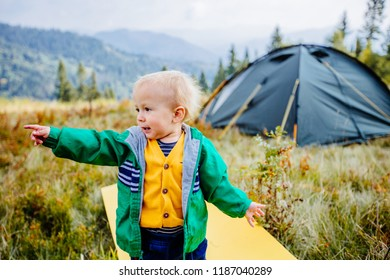 Emotional portrait of cute toddler boy traveler pointing by finger on something in camping with tent on background. Travel with child, health relations concept.