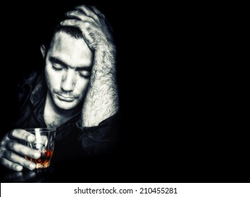 Emotional portrait of a drunk man holding a glass of whisky on a black background