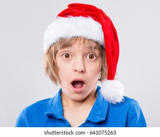 Emotional portrait of excited little girl wearing Santa Claus red hat. Funny cute surprised child 10 year old with mouth open in amazement on gray background. Winter holiday christmas concept.