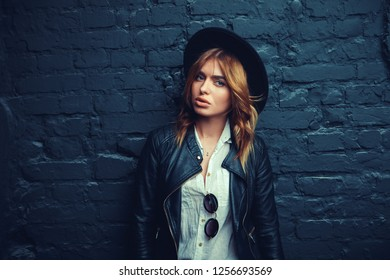 Emotional portrait of Fashion stylish portrait of pretty young hipster blonde woman,going crazy,elegant black hat,soft colors,cool crazy  girl.Red urban wall background.surprised,close up,isolated