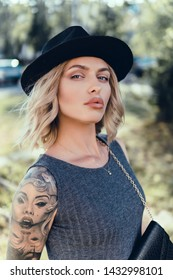 emotional portrait of Fashion stylish portrait of pretty young hipster blonde woman,going crazy,elegant black hat,soft colors,cool crazy  girl.Red urban wall background.surprised girl close up, sunset