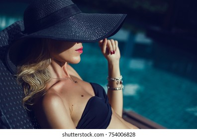 Emotional portrait of Fashion stylish portrait of pretty young hipster blonde woman posing in the swimming pool. hat, swimsuit, outdoor fashion portrait  ,going crazy,elegant black hat cool