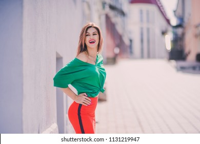 emotional portrait of Fashion stylish sexy of  young hipster blonde woman, elegant lady, green top and red skirt, cool  girl. City view  urban lifestyle background.