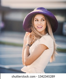 emotional portrait of Fashion stylish sexy of  young hipster blonde woman, elegant lady, bright colors dress, cool  girl. City view  urban lifestyle background with purple hat