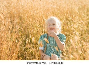 Emotional portrait of a funny and cheerful little blonde girl with pigtails, laughing at a joke sitting in a wheat field in the rays of sunset. Summertime. Summer vacation. Happy childhood. Positive