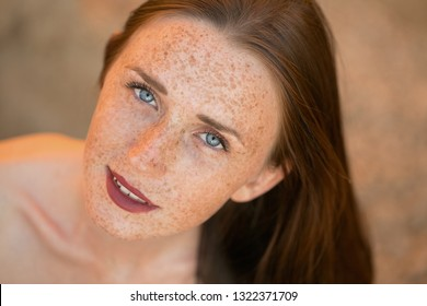 Emotional portrait of a happy and calm beautiful naked girl with freckles on her face and blue eyes looking up during a summer holiday on the sea. Summertime. Lifestyle. Summer vacation. Girl in beach
