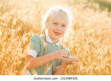 Emotional portrait of a happy and cheerful beautiful little girl with blond hair and pigtails, looking with a smile at her mom, sitting in a field of wheat in the rays of the setting sun. Summer