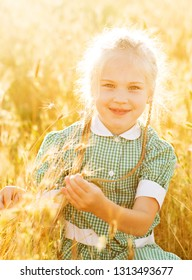 Emotional portrait of a happy and cheerful beautiful little girl with blond hair and pigtails, looking with a smile at her mom, sitting in a field of wheat in the rays of the setting sun. Summer life