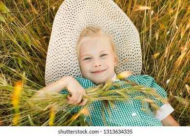 Emotional portrait of a happy and cheerful beautiful little girl in a hat looking with a smile at the sky while holding spikelets in her hand while lying in a wheat field. Childhood.Summertime. Summer