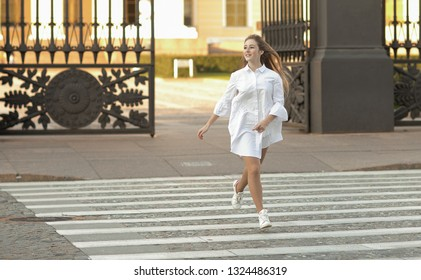 Emotional portrait of a happy and cheerful beautiful teenager girl running through a pedestrian crossing during a walk through the city. Girl in summer city. Summertime. Lifestyle. Positive energy
