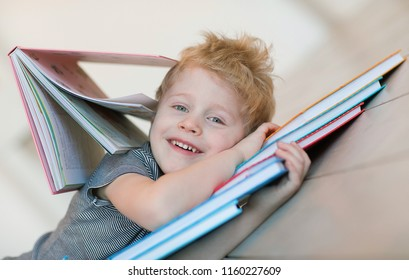 Emotional portrait of a happy and cheerful little boy with blond hair, looking with a mischievous smile in the camera lying on a pile of books and hugging them after reading classes in kindergarten