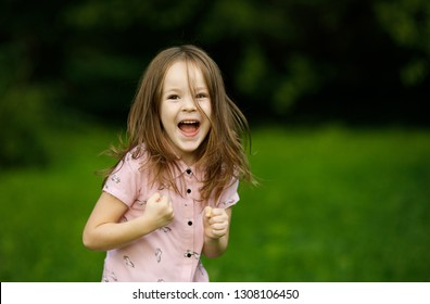 Emotional portrait of a happy and cheerful little girl laughing while looking at her mom while playing in the park on the background of blurry trees. Summertime. Summer vacation. Childhood. Positive