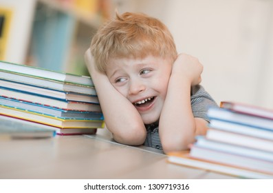 Emotional portrait of a happy and cheerful little boy with blond hair laughing at a joke lying on the floor among the stacks of children's books in the room. Childhood. Positive emotions and energy