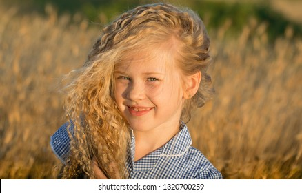 Emotional portrait of a happy and cheerful little girl with blond curly hair, shyly looking with a smile at the camera while standing in a wheat field at sunset. Childhood. Summertime. Summer vacation