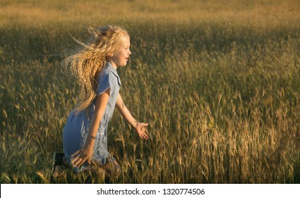 Emotional portrait of a happy and cheerful little blonde girl running with a laugh over a wheat field lit by the rays of the setting sun. Happy childhood. Summertime. Summer vacation. Positive energy