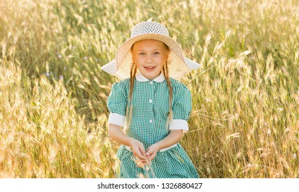 Emotional portrait of a happy and cheerful little blonde girl with pigtails and a hat looking with a smile at her father sitting in a wheat field in the sunset light. Childhood. Summer vacation.