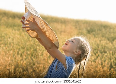 Emotional portrait of a happy and cheerful little girl with curly blond hair throwing her hat up to the sky with a smile standing in a wheat field in the rays of the sunset. Childhood. Summer