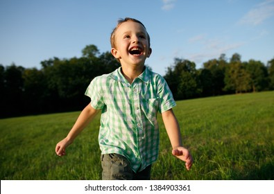 Emotional portrait of a happy and cheerful little boy, running after a friend laughing while playing on a walk in the park. Happy childhood. Summertime. Summer vacation. Positive emotions and energy