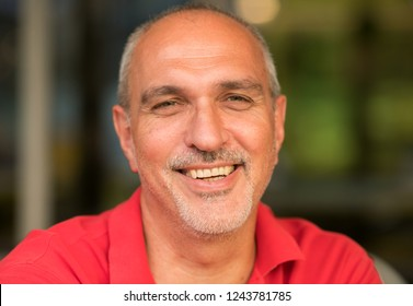 Emotional portrait of a happy and cheerful mature tanned European man with a bald head looking with laughter at the camera against the windows. Summer travel. Lifestyle. Man in city. Summertime
