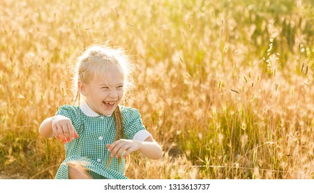 Emotional portrait of a happy and energetic beautiful little girl with blond hair and pigtails, looking with a laugh at her sister, sitting in a field of wheat in the rays of the setting sun. Summer