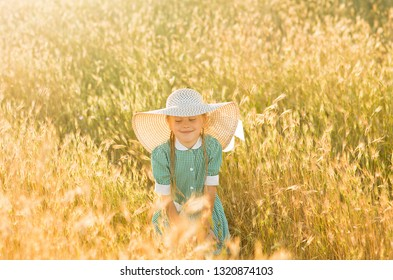 Emotional portrait of a happy and funny little blonde girl, with a smile on her face looking at the wheat spikelets illuminated by the rays of the setting sun. Summertime. Summer vacation. Childhood