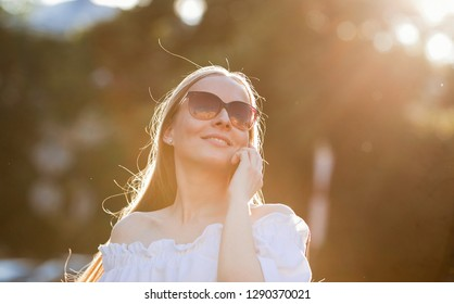 Emotional portrait of a happy and gentle beautiful girl in sunglasses, talking with a smile on a smartphone and looking up in the sun on a walk in the city. Lifestyle. Woman in summer city. Summertime