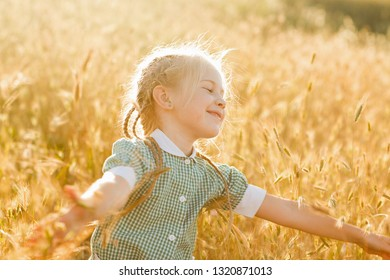 Emotional portrait of a happy and kind little fair-haired girl, with a smile on her face trying to hug mature wheat ears covered with the rays of the setting sun. Happy childhood. Summertime. Summer