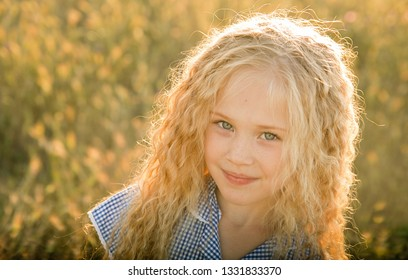 Emotional portrait of a happy and kind little girl with curly blond hair looking with a smile at the camera while sitting in a wheat field and lit by the rays of the setting sun. Childhood. Summer