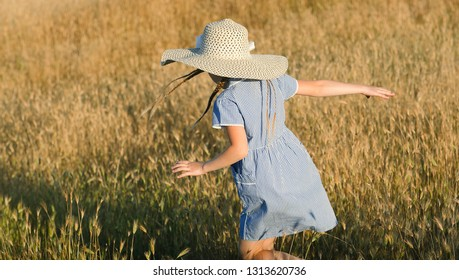Emotional portrait of a happy and mischievous beautiful little girl in a hat running through a wheat field lit by the setting sun. Summertime. Happy childhood. Summer vacation. Positive emotions