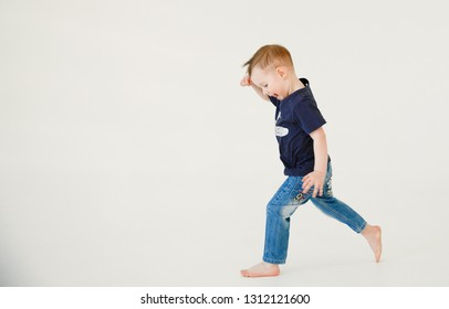 Emotional portrait of a happy and mischievous little boy escaping with laughter in a white room from an older brother. Copy space. Happy childhood. Positive emotions and energy. Lifestyle.