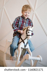 Emotional portrait of a happy and positive little boy with blond hair and a checked shirt, swaying with a smile on a wooden horse in his room. Children's rocking chair. Happy childhood. Lifestyle