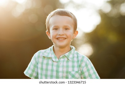 Emotional portrait of a happy and positive little boy looking ahead with a smile lit by the rays of the setting sun against a background of blurred leaves.Childhood. Summertime.Summer vacation