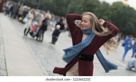 Emotional portrait of a happy and positive young beautiful woman with blond hair, dancing with closed eyes against the background of the square for a walk in the city. Girl in summer city. Lifestyle